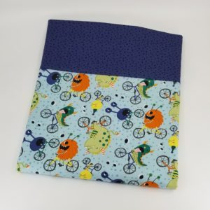Pillowcase with pattern of silly monsters riding bicycles, light blue background, dark purple dot border