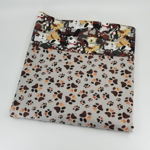 Pillowcase with pattern of dog paw prints on a light grey background border fabric of happy dogs