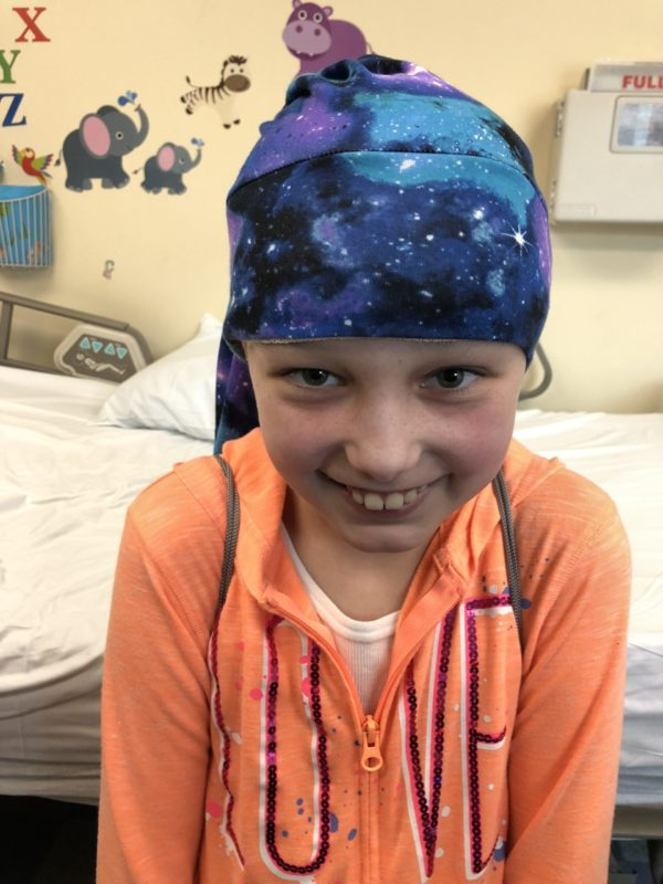 Child wearing a NillyNoggin(tm) cap during an EEG test