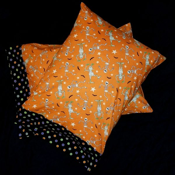 Halloween themed pillowcase with pattern of glow-in-the-dark skeletons and zombies, orange background, border of colorful dots on black
