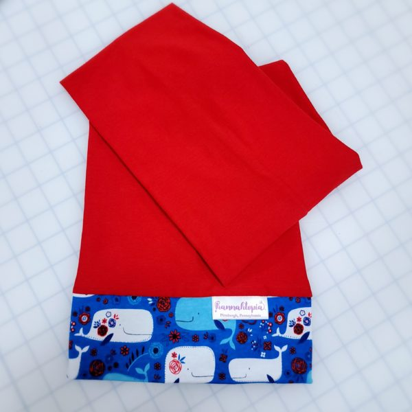 Red length with Blue band decorated with blue and white happy whales NillyNoggin EEG Cap folded