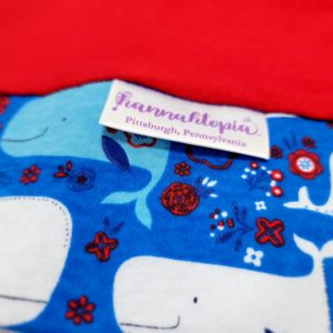 Red length with Blue band decorated with blue and white happy whales NillyNoggin EEG Cap close up of fabric