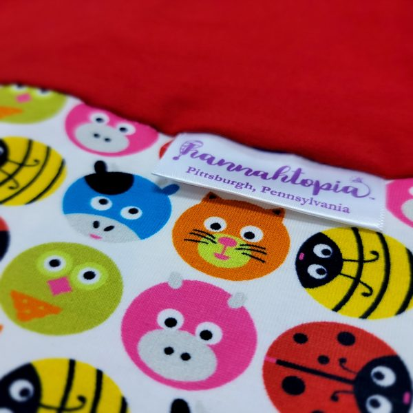 Red and Circle Shapes of Pigs, Cats, Cows, Bumble Bees and Lady Bugs NillyNoggin EEG Cap close up of fabric