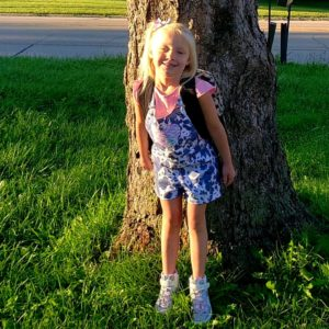 girl standing by tree